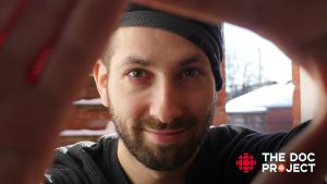 Aquil wears a toque in wintery Ottawa and smiles at the camera with The Doc Project logo in the corner.